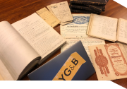 Genealogy documents and a laptop with an NYG&B logo